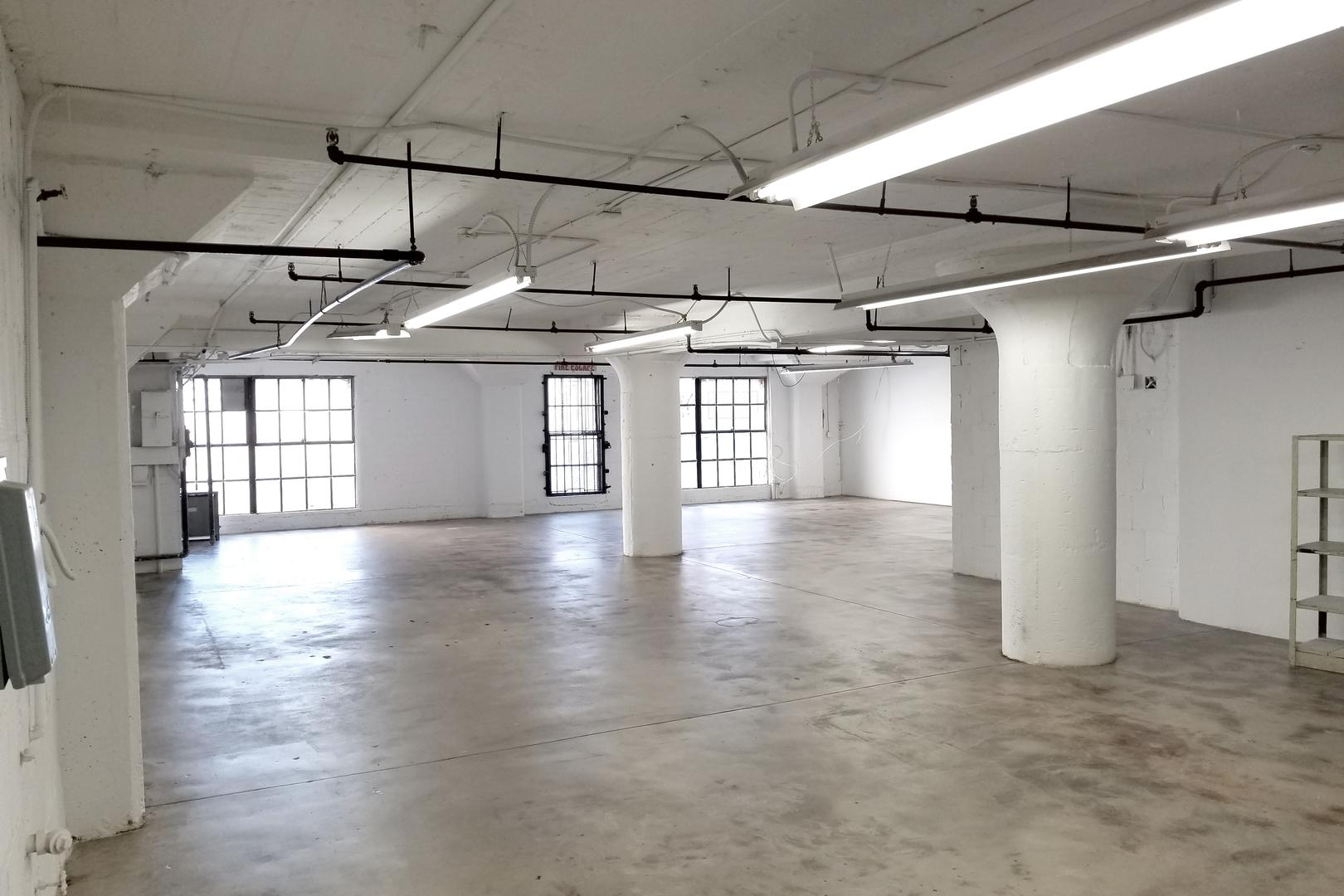 space at Downtown Studio Loft With Concrete and White Wall Large Windows With Lots Of Natural Light